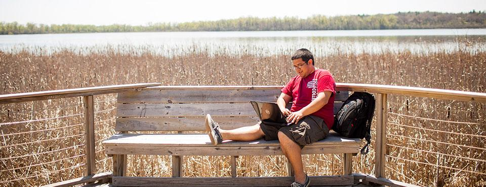 Student studying by lakeshore